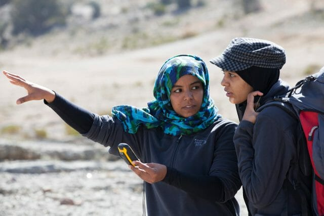Female Omani guide using compass