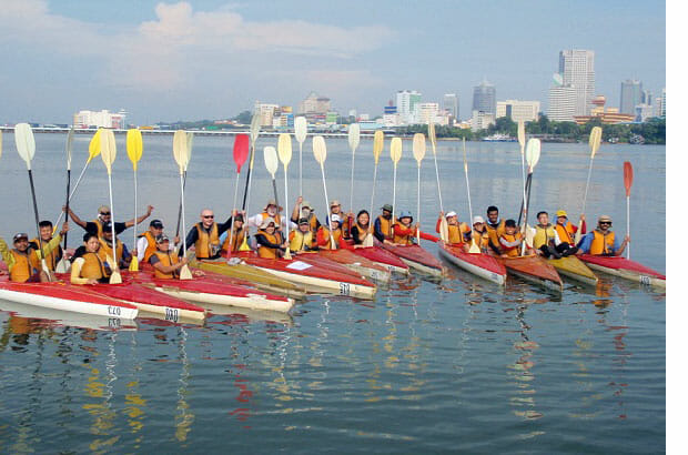 Kayakers raising their paddles in vietnam