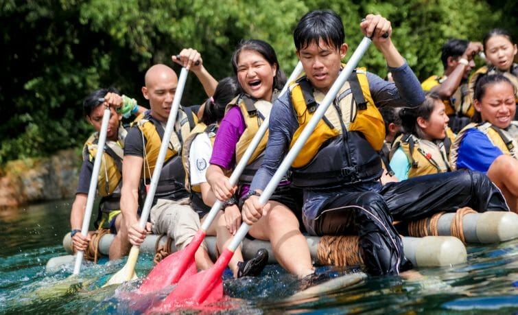Youth paddling bamboo raft