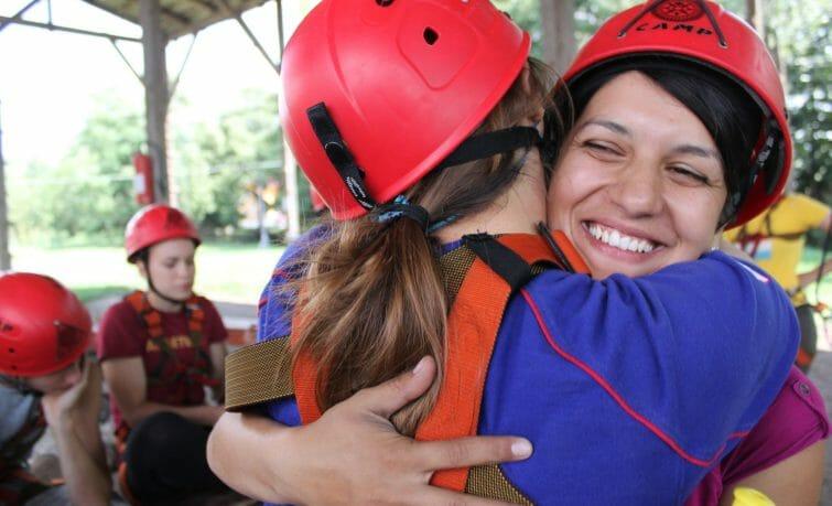 Two climbing girls hugging